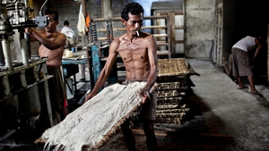 A factory worker carries noodles to be steamed in Srandakan village, Bantul, Indonesia
