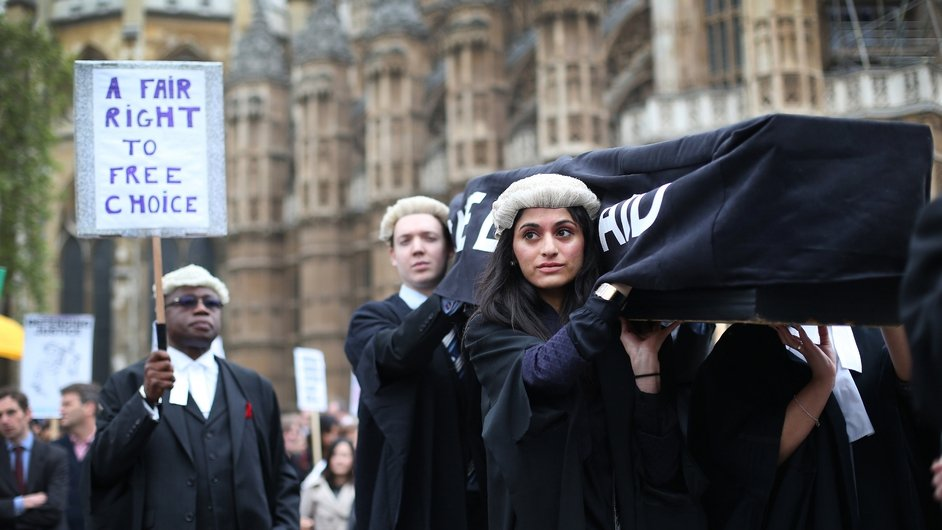 Demonstrators carry a coffin representing the death of Legal Aid near London's Parliament Buildings