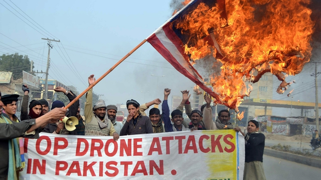 A Pakistani demonstrator holds a burning US flag during a recent protest  against the drone attacks