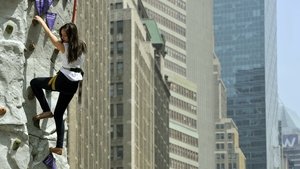 A woman climbs a nine metre climbing wall in Herald Square, New York during an event called Grape-Nuts 'What's Your Mountain' in celebration of Post Grape-Nuts' role in Sir Edmund Hillary's historic ascent of Mt Everest 60 years ago