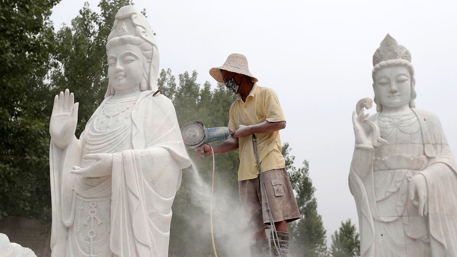 A worker polishes a sculpture at the Zhenping county jade factory, in Shifosi, Henan province, China