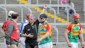 Carlow's Shane Kavanagh (r) is shown a red card by referee Johnny Ryan; Carlow had three men sent off in the 2-18 to 0-13 defeat
