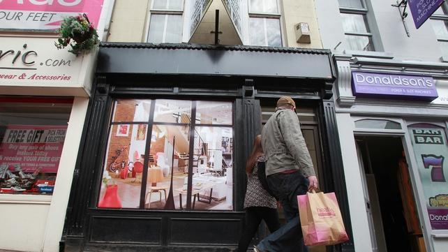 Pedestrians walk by a fake shop front in Enniskillen