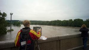 An artist paints the overflooding Vltava river in Prague.