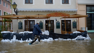 A man walks past a restaurant surrounded by the floods of the river Elbe in Pirna, eastern Germany