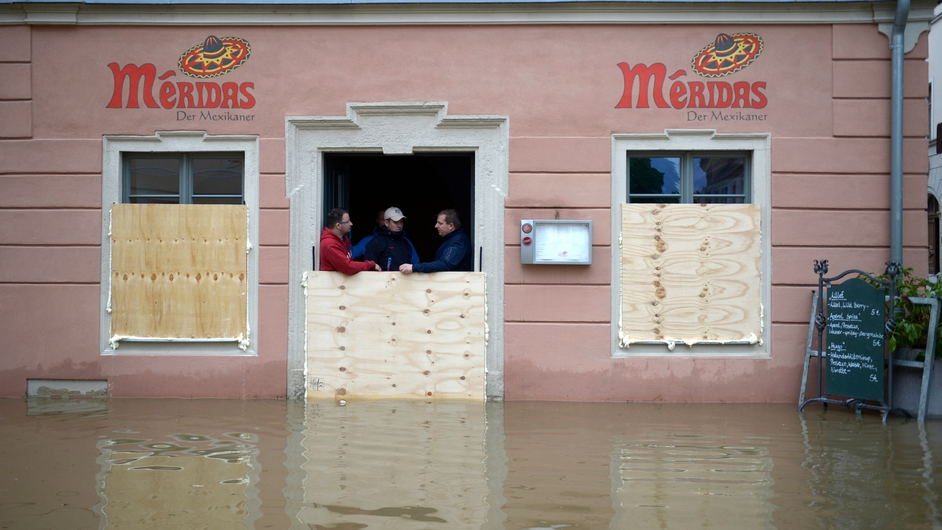 Three men stand behind wooden panels erected to protect a restaurant against the floods of the river Elbe in Pirna, eastern Germany