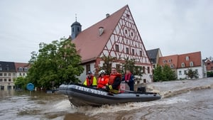 Firefighters and helpers evacuate inhabitants in the flooded city centre in Grimma, Germany.