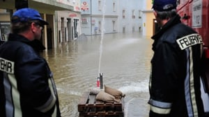 Two firefighters stand next to a pump in the flooded streets of the historic city centre in Passau, Germany.