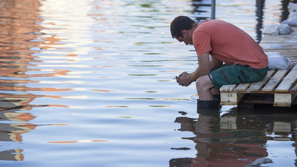 A helper sitting on a provisional footbridge in the flooded city centre in Bernburg, Germany
