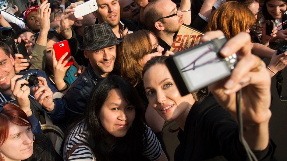 Angelina Jolie takes a photo of herself with a fan's camera as she poses with fans upon her arrival for the Paris premiere of 'World War Z'