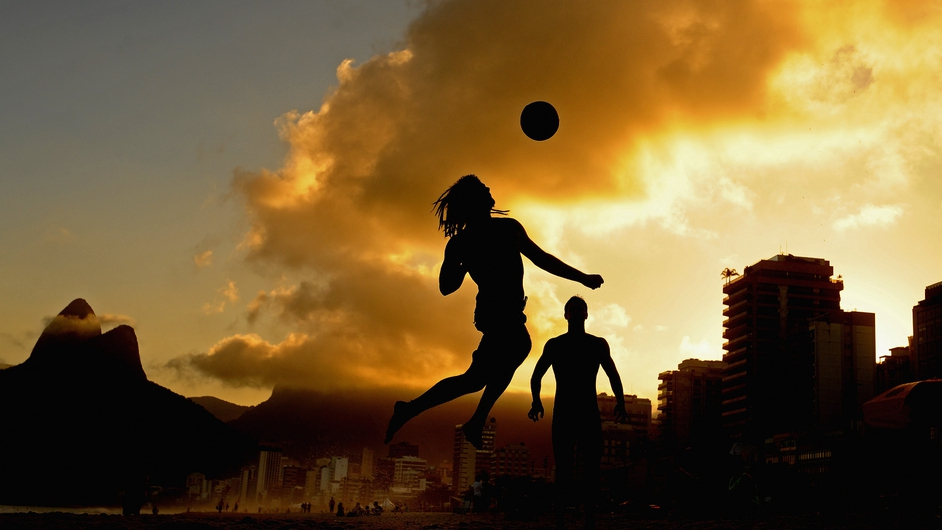 A man plays football on Ipanema beach in Brazil