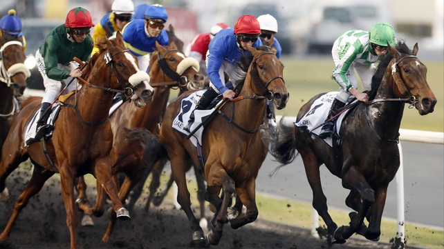 Lines Of Battle (right) leads the field on his way to victory in the UAE Derby
