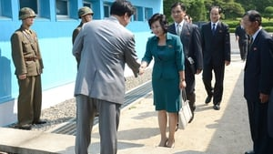 South Korea's delegate (L) shakes hands with North Korea's head of working-level delegation Kim Song-Hye (R) as she crosses the military demarcation line for the meeting at Pammunjon