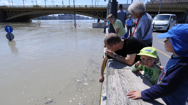 A man measures the height of the swollen river Danube