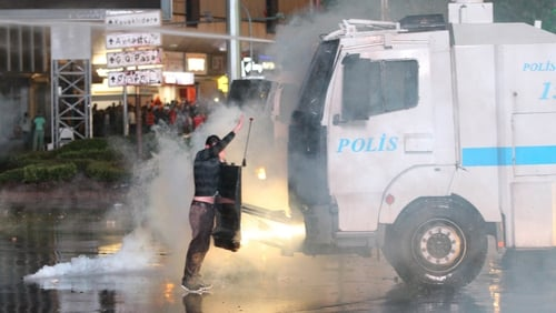 Protesters take cover from water cannon during clashes with police at a demonstration in Ankara