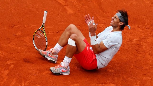 Rafael Nadal sinks on to the red clay of Court Philippe Chatrier after dispatching his backhand winner on match point