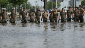 Soldiers of the German Bundeswehr walk through flood waters from the swollen Elbe river