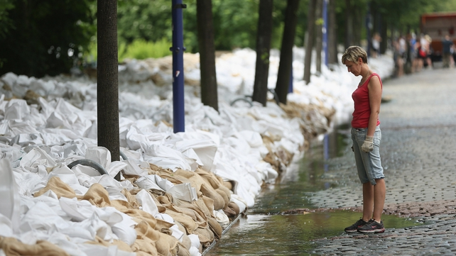 A woman looks at sandbags stacked against the rising flood waters of the river Elbe