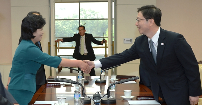 South Korea's senior Unification Ministry official and head of working-level delegation Chun Hae-Sung (R) shakes hands with his North Korean counterpart Kim Song-Hye (L)