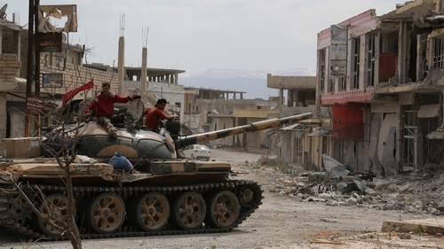 Syrian army soldiers drive a tank through the sacked town of Qusair