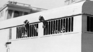 Nelson Mandela is among eight men sentenced to life in prison in June 1964. Some raise their fists in defiance through the barred windows of a prison car