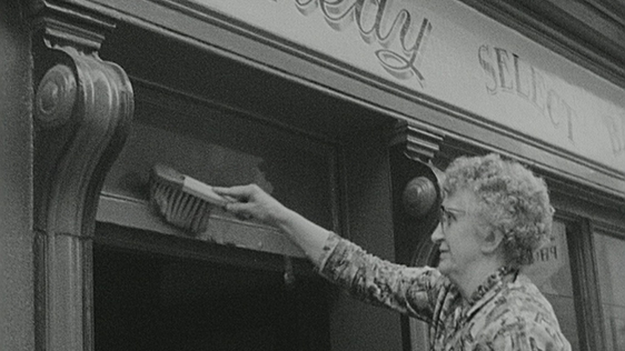 Shopkeeper cleaning front of shop in New Ross, Co. Wexford in preparation for President Kennedy's arrival.