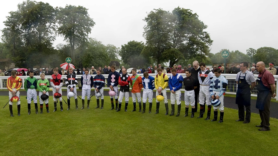 Tom Queally (yellow and red silks) bows his head during a minute's silence for Henry Cecil at Salisbury