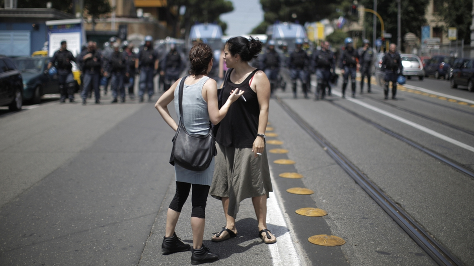 Students look on as police block a street in Rome on the eve of the 2009 summit in Italy
