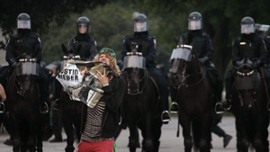 A protester destroys a poster of Justin Bieber as mounted riot police look on in Toronto, Canada in 2010