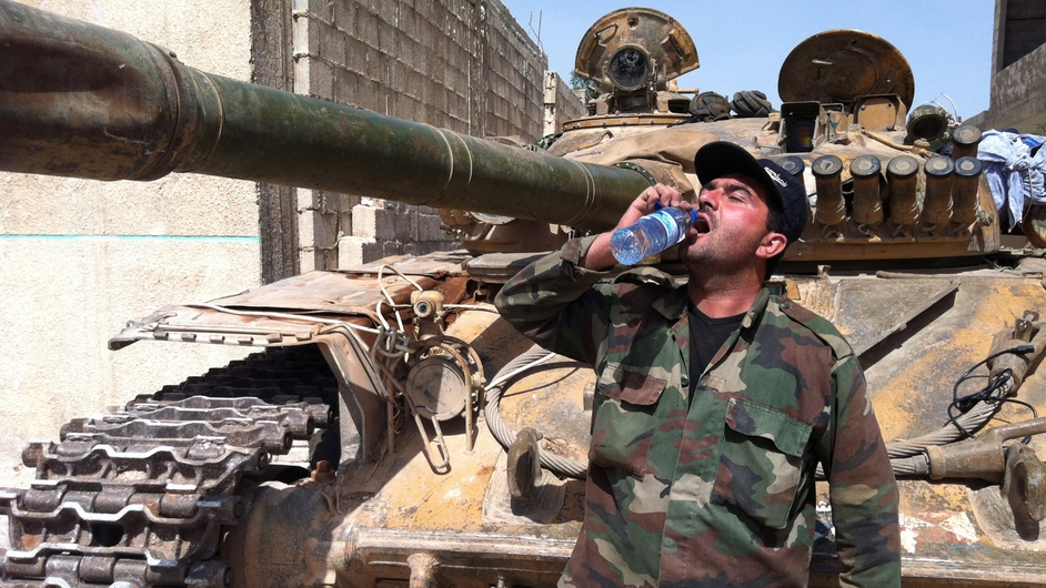 A Syrian army soldier drinking water next to an army tank in the village of Buweida, north of Qusair, as government troops seized the area