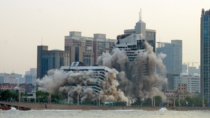 Smoke and dust rise as a 27-year old hotel building is demolished in Qingdao, in east China's Shandong province