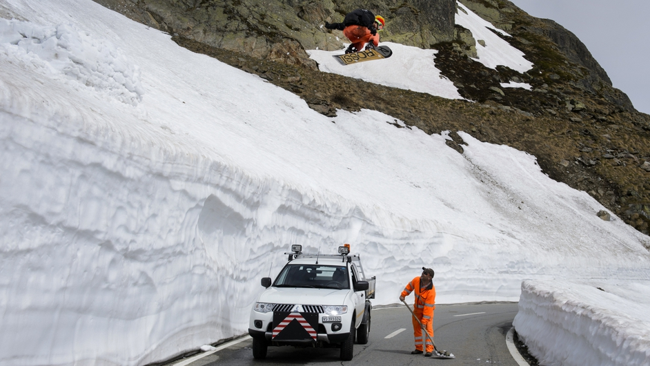 A snowboarder jumps over a road maintenance crew taking off the last snow on a mountain pass road after exceptional snowfalls in Switzerland