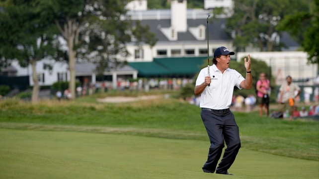 Mickelson watches his putt roll to the hole