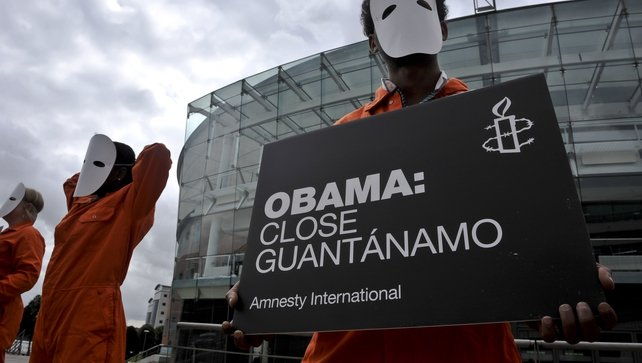 Protesters from Amnesty International in Belfast hold placards requesting that the US closes Guantanamo
