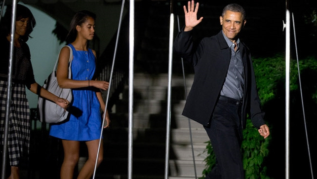 Barack Obama is followed by First Lady Michelle Obama and their daughter Malia as they depart the White House