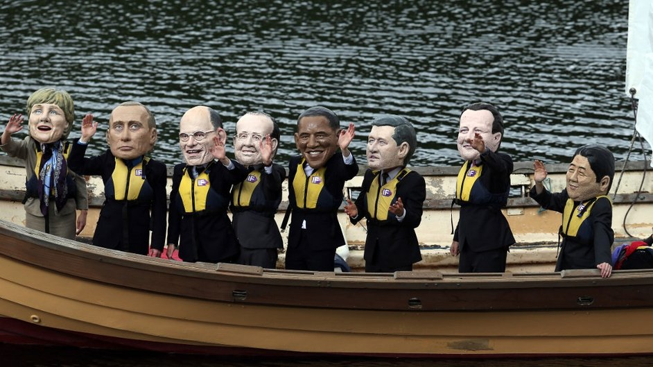 Protesters wearing masks of the G8 Leaders stand in a boat on Lough Erne during the first day of the G8 Summit