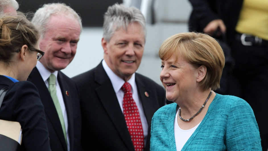 German Chancellor Angela Merkel (R) is greeted by Peter Robinson and Martin McGuinness as she arrives at Belfast International Airport