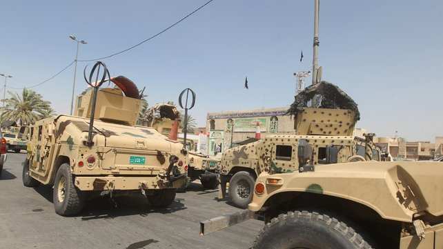 Iraqi military vehicles are stationed in front of the Shia Muslim mosque in Baghdad