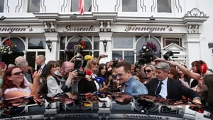 Bono is mobbed by fans (and a few journalists) as he leaves the pub in Dalkey