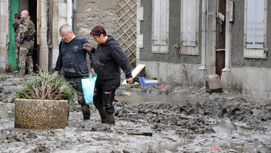 Villagers make their way through the mud-caked streets of Saint-Beat