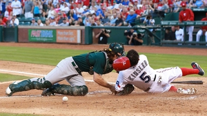 John Jaso (l) of the Oakland Athletics drops the ball after colliding with Ian Kinsler of the Texas Rangers