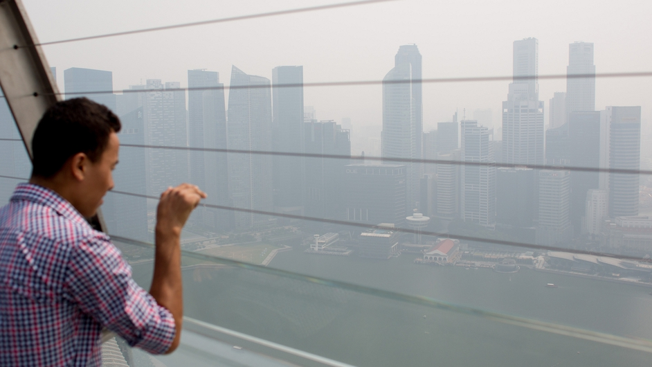 A man looks out over the smoke filled Singapore skyline