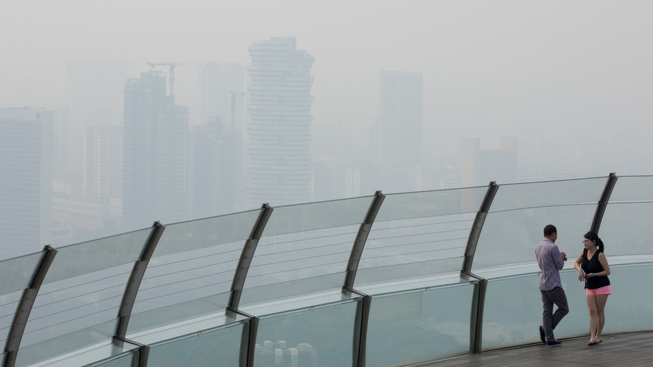 Two people look out over the smoke shrouded Singapore skyline from the Marina Bay Skypark