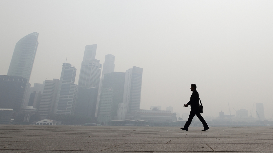 A man walks in front of the Singapore city skyline