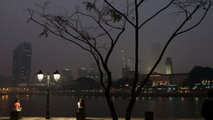 People sit by the Singapore River