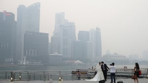 A couple poses for a pre-wedding photograph as the city skyline is filled with smog at the Marina Bay Waterfront in Singapore