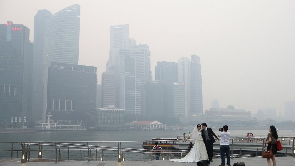 A couple takes a pre-wedding photograph as the city skyline is filled with smog at the Marina Bay Waterfront