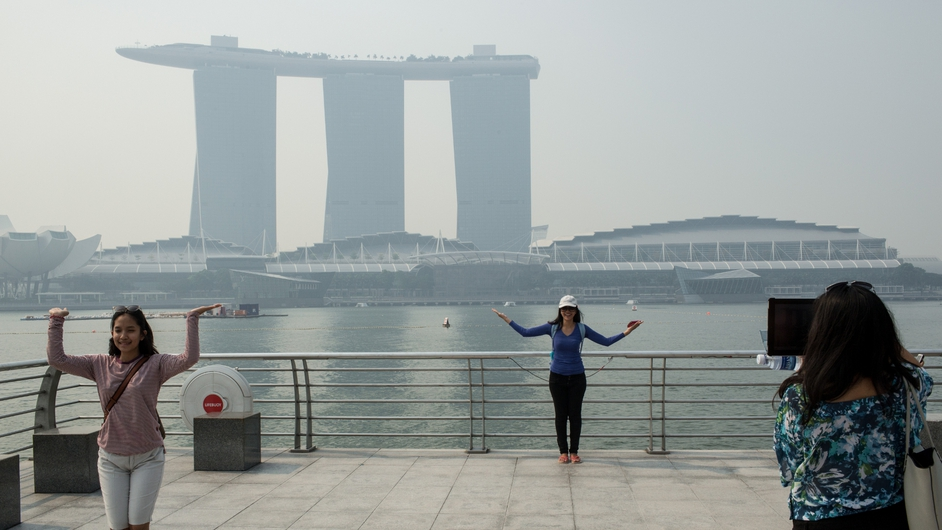 Tourists pose for photographs in front of the Marina Bay Sands hotel