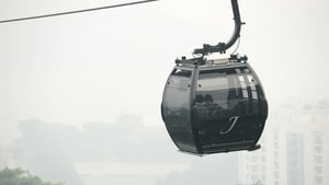 Tourists ride in a cable car as their surroundings are blanketed by haze