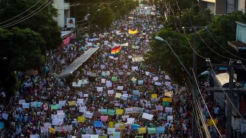 Thousands of people march on Avenida Conde Boa Vista, in the state of Pernambuco, Brazil